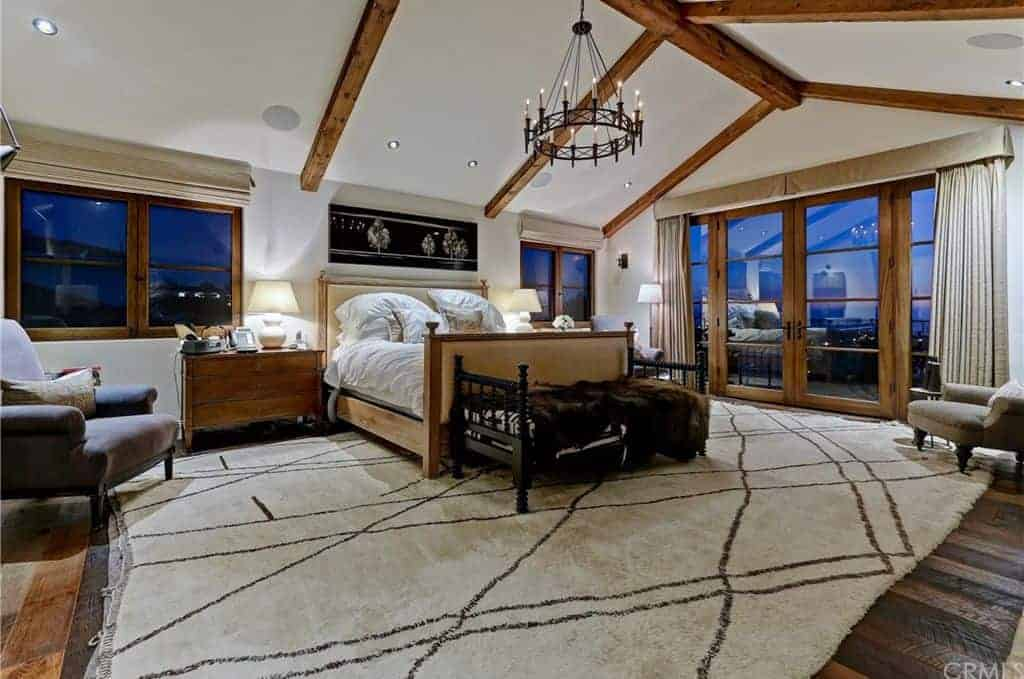 The cozy master bedroom features a beige upholstered bed with a black cushioned seat on its end over a shaggy area rug. It is illuminated by white table lamps and a wrought iron chandelier that hung from the cathedral ceiling with exposed beams.