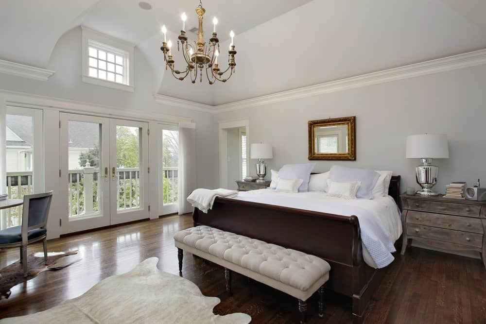 White primary bedroom with vaulted ceiling and hardwood flooring topped by cowhide rugs. It includes a dark wood bed with a beige tufted bench on its end along with chrome table lamps that sit on rustic nightstands.