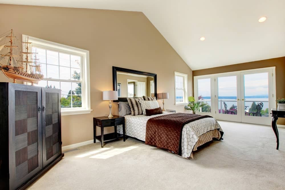 This master bedroom showcases a comfy bed under a black framed mirror along with a dark wood cabinet that's topped with a gorgeous ship decor. It has carpet flooring and a French door leading out to the balcony with a magnificent view.