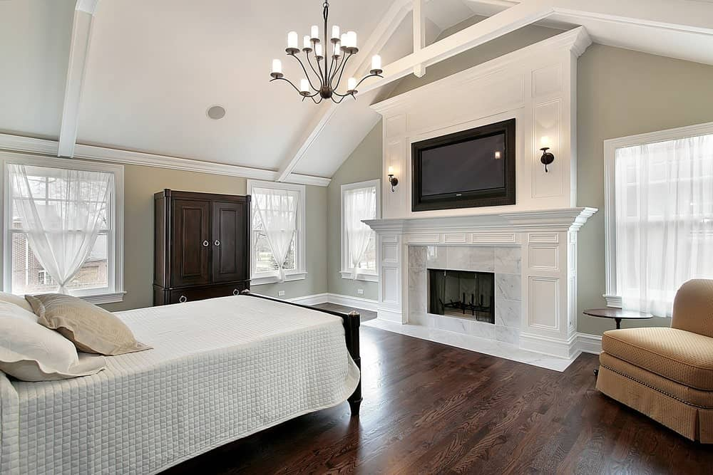 The gray primary bedroom showcases a skirted chair and wooden bed facing the fireplace and wall mount TV. It is illuminated by a wrought iron chandelier that hung from the cathedral ceiling.