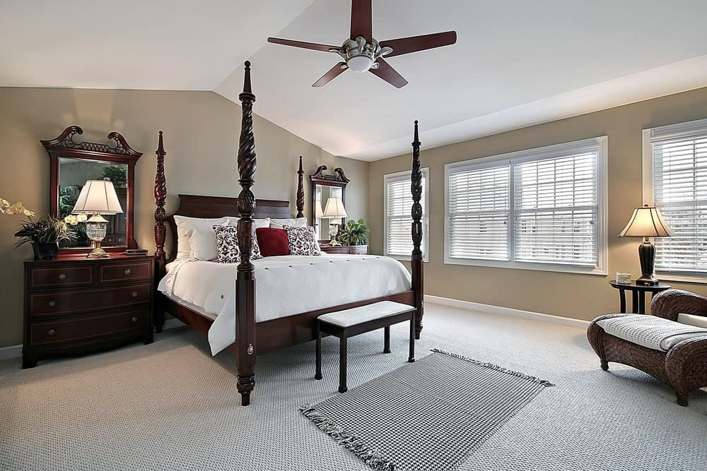 The classic primary bedroom offers a four-poster bed with dark wood nightstands on the sides along with a lounge chair paired with a round side table that's topped with a traditional table lamp. It includes a ceiling fan and a tasseled rug that lays on the carpet flooring.