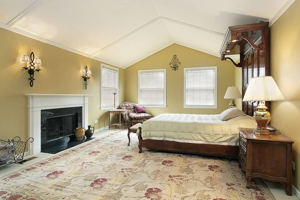 A patterned lounge chair faces the wooden bed that's fitted with a large custom headboard. It is accompanied by matching nightstands and a fireplace lighted by wall sconces.