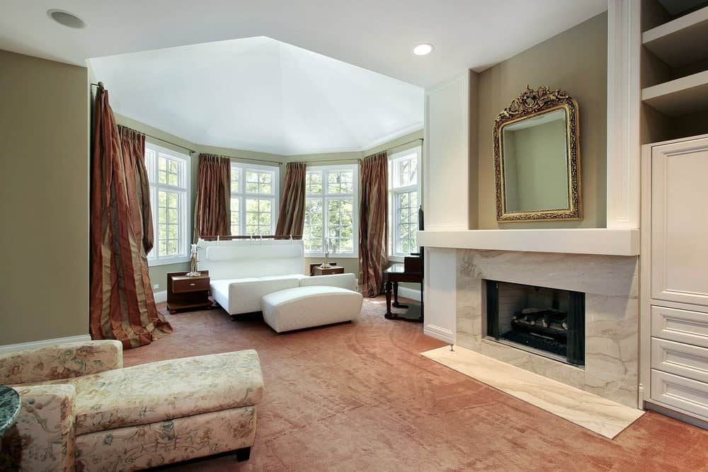 Elegant primary bedroom with carpet flooring and white framed windows dressed in classy striped draperies. It includes a white bed and a floral chaise lounge facing the fireplace with a gorgeous mirror on top.