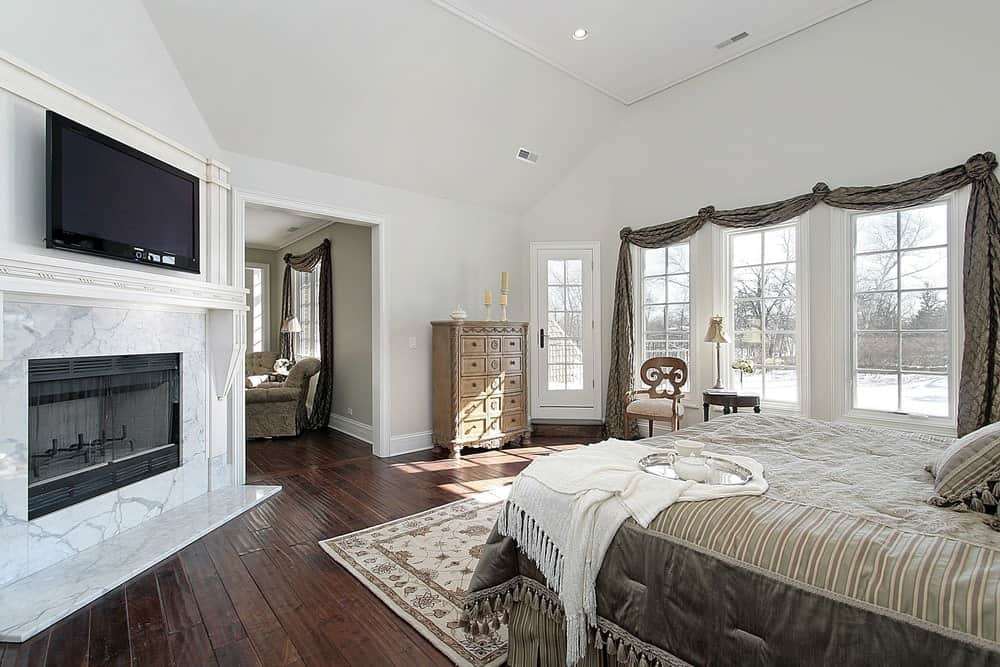 Natural light streams in through the glazed windows in this primary bedroom with a skirted bed and a floral rug that lays on the natural hardwood flooring. It includes wall mount TV and a corner fireplace framed in white marble surround.