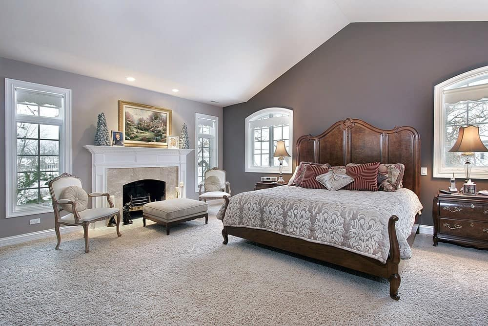 This primary bedroom boasts a wooden bed and a seating area by the fireplace that's topped with framed photos and a gorgeous landscape painting. It has carpet flooring and vaulted ceiling mounted with recessed lights.