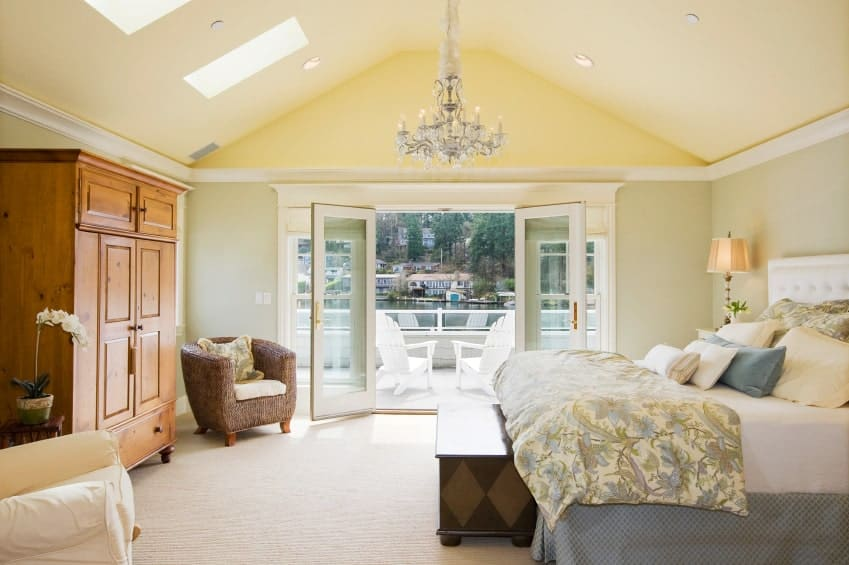 Bright primary bedroom with mismatched seats and a white tufted bed lighted by a fancy candle chandelier. It has carpet flooring and a French door that opens to the balcony filled with white armchairs.