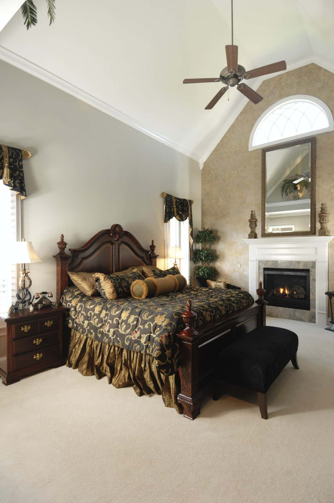 A wooden bed dressed in green floral bedding complements the classy valances covering the glazed windows. This primary bedroom features a fireplace and a chrome fan that hung from the high vaulted ceiling.