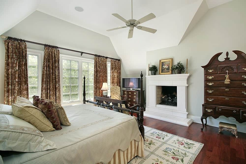 The sophisticated master bedroom offers a four-poster bed over a floral area rug along with a white fireplace flanked by wooden dressers that are accented with elegant brass hardware.