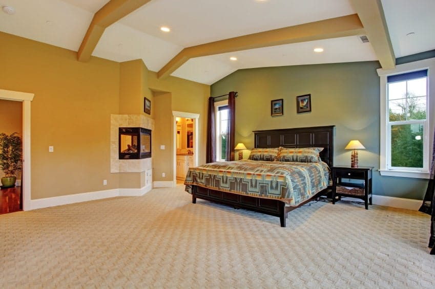 Spacious master bedroom with textured carpet flooring and white framed windows inviting natural light in. It includes a corner fireplace and a cozy bed complementing with the dark wood nightstands that are topped with small table lamps.