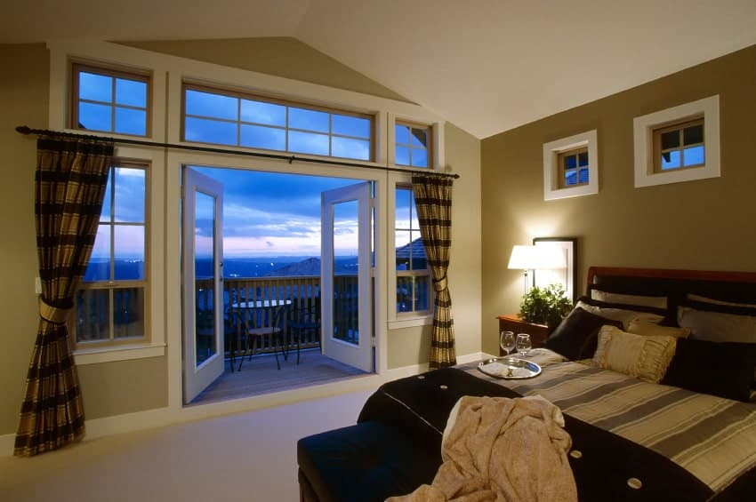 Warm master bedroom with a cathedral ceiling and a French door that opens to the balcony with an expansive view. It includes a comfy bed with a black ottoman on its end lighted by a table lamp that sits on a wooden nightstand.