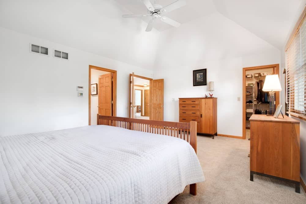 White master bedroom furnished with wooden dressers and a cozy bed wrapped in a textured blanket. It has beige carpet flooring and a vaulted ceiling mounted with a fan.