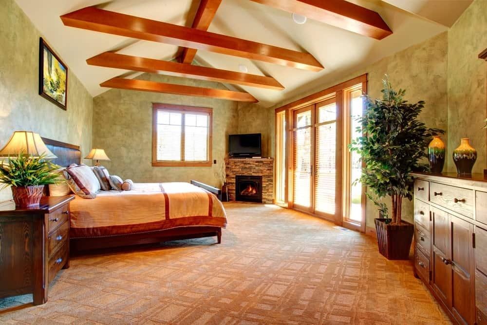 This master bedroom showcases a wooden bed and cabinet with a large potted plant on the side along with a TV and brick fireplace fixed in the corner. It has carpet flooring and cathedral ceiling lined with wood beams.