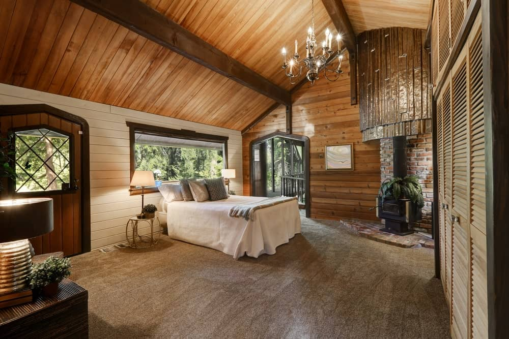 Cozy master bedroom illuminated by a candle chandelier that hung from the cathedral ceiling clad in wood planks. It has a white bed and a freestanding fireplace fixed against the brick pillar.