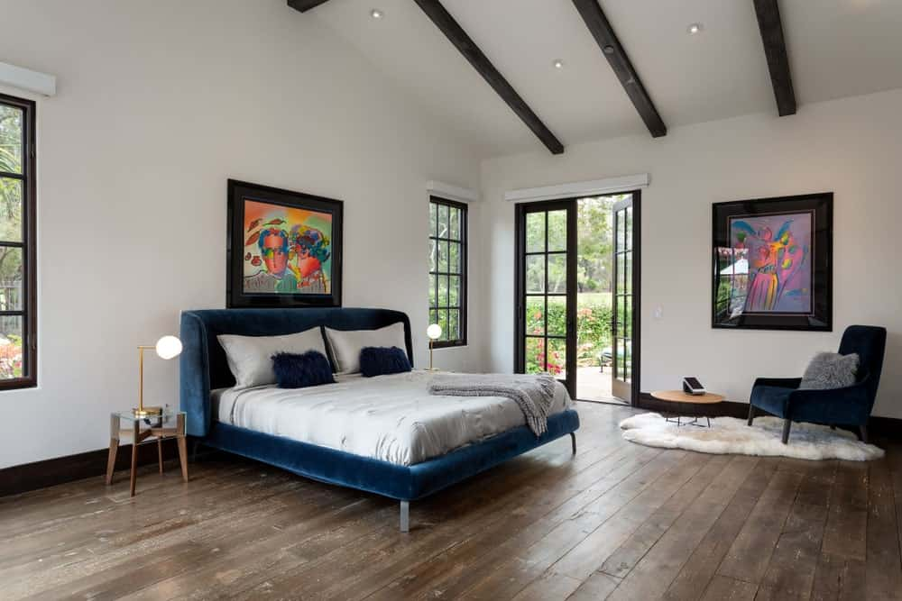 An airy master bedroom decorated with interesting artworks that are mounted on the white walls. It has deep blue velvet bed matching with the chair on a white faux fur rug over wide plank flooring.