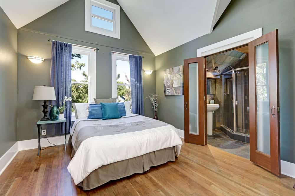 Glass sconces flank white framed windows that are covered in blue curtains. This primary bedroom has a skirted bed with a metal nightstand on the side along with a wooden double door that opens to the bathroom.