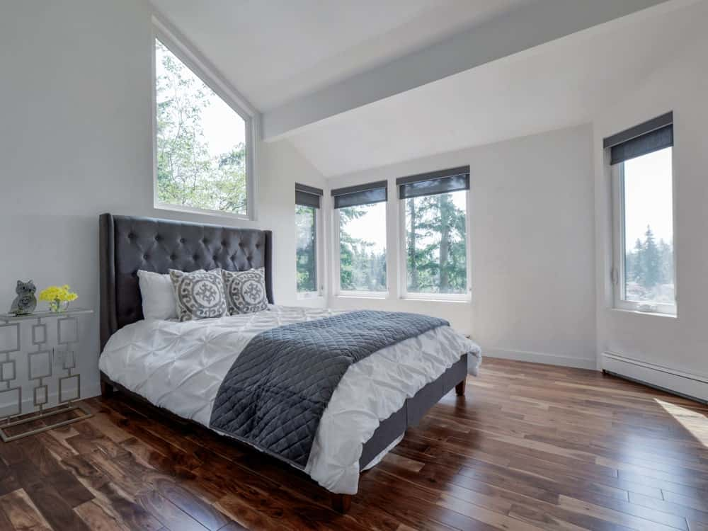 The white primary bedroom offers a leather tufted bed and a stylish nightstand on the side topped with glass flower vase and animal decor. It has natural hardwood flooring and plenty of picture windows allowing an abundance of natural light in.