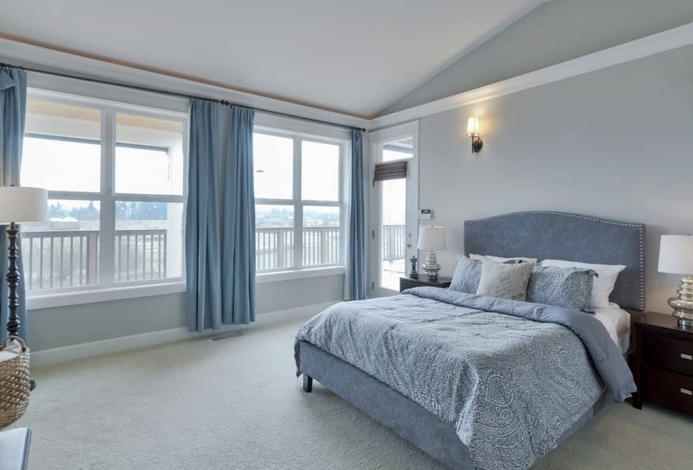 Bright primary bedroom with dark wood nightstands and a gorgeous blue bed complementing with the draperies that cover the white-framed windows. It is lighted by chrome table lamps and an iron sconce mounted on the light gray wall.