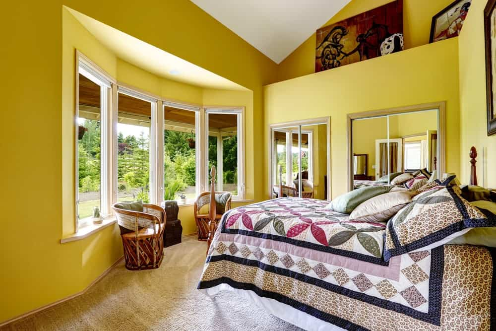 Yellow primary bedroom boasts a four-poster bed dressed in floral and diamond-patterned bedding along with wooden round back chairs by the bay window bringing plenty of natural light in.