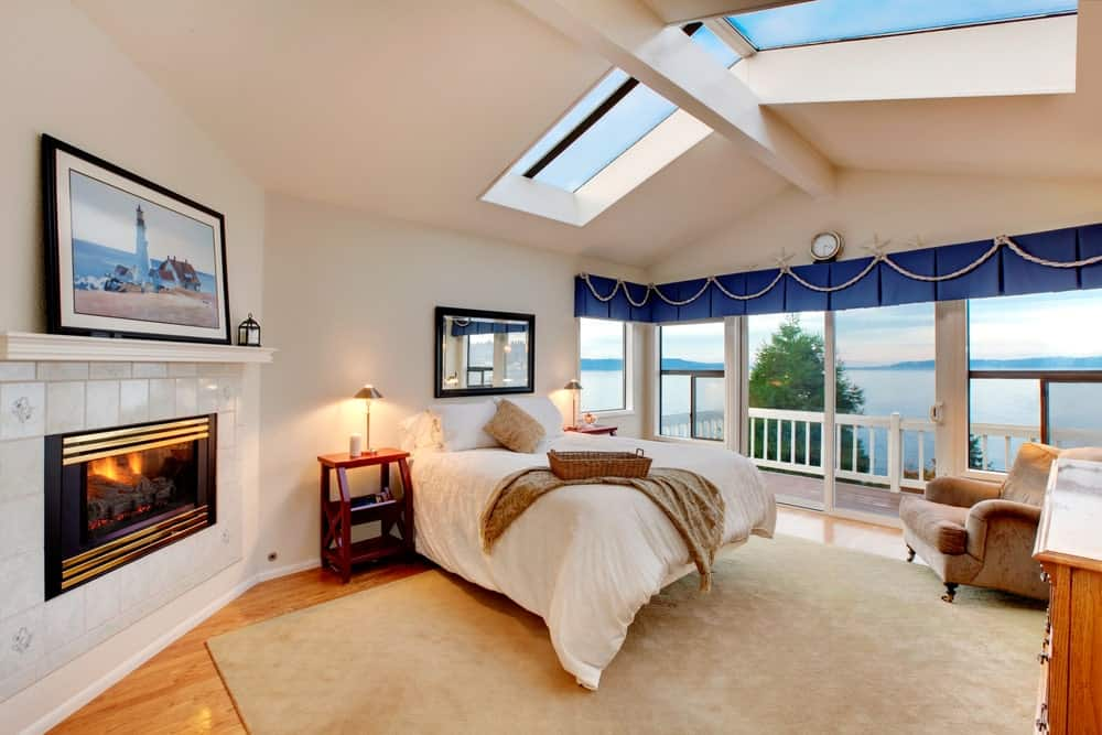 This primary bedroom features a tiled fireplace and a comfy bed underneath the skylights fitted on the cathedral ceiling. It has hardwood flooring and glass sliders leading out to the balcony with a breathtaking beachfront view.
