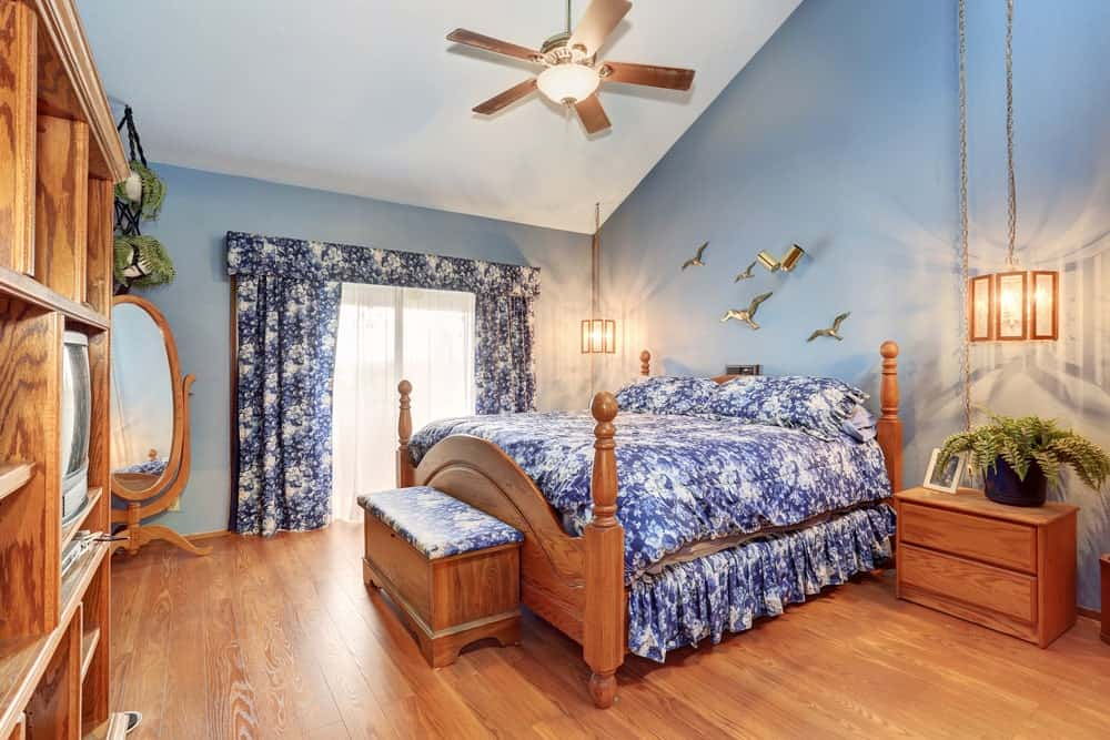 Blue floral bedding matches the valance and draperies in this master bedroom with open shelving and wooden nightstands that blend in with the hardwood flooring. It is illuminated by stylish pendant lights that hung from the cathedral ceiling.