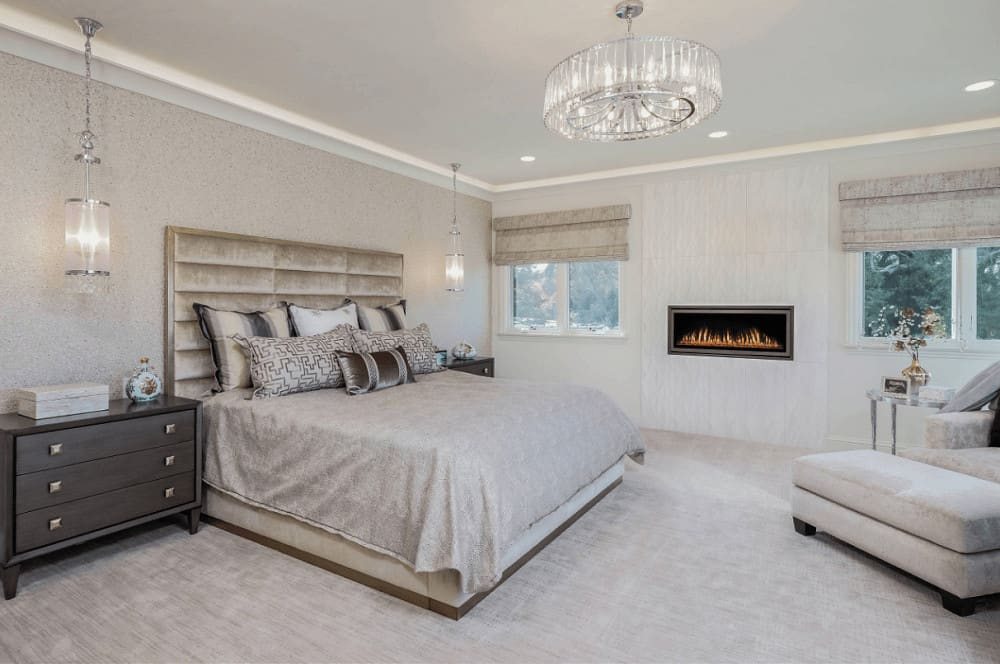 A pair of chrome pendant lights hang over the dark wood nightstands in this Mediterranean bedroom boasting a velvet bed and a modern fireplace mounted in between the white framed windows.