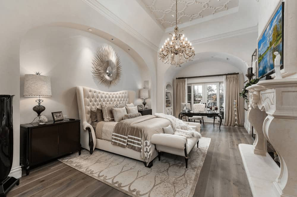 Mediterranean bedroom decorated with a sunburst mirror and fabulous chandelier that hung from the ornate tray ceiling. It has a carved fireplace and a tufted wingback bed with dark wood nightstands on its sides placed on the arched inset wall.