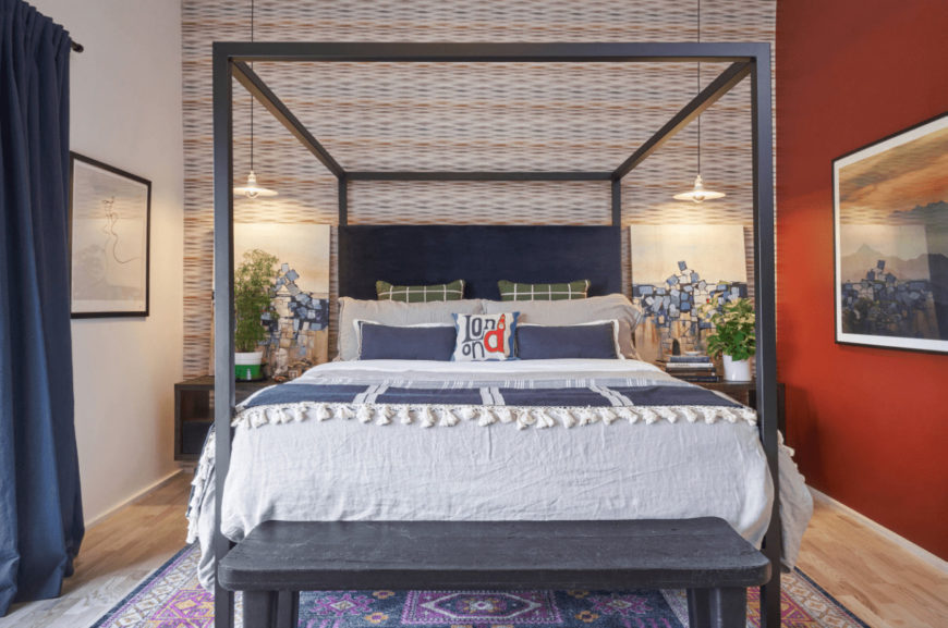 A purple floral rug lays on the light hardwood flooring in this bedroom with a canopy bed flanked by wooden nightstands and lovely artworks that are lighted by dome pendants.