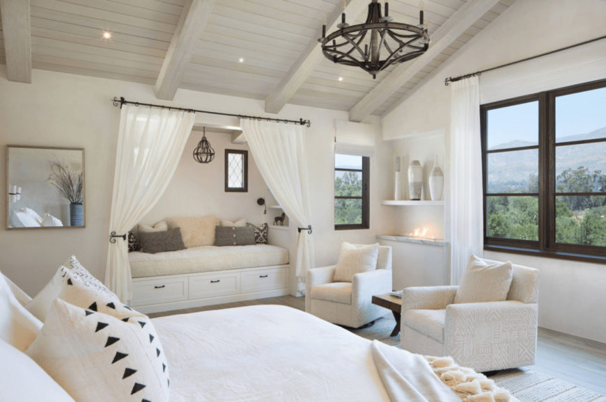 An all white bedroom with a comfy bed and armchairs along with a seat nook completed with white sheer curtains. It is illuminated by a vintage chandelier and recessed lights fitted on the wood beam ceiling.