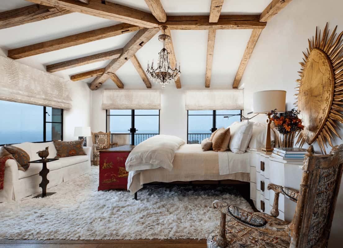 Mediterranean bedroom designed with a large sun decor and a fancy chandelier that hung from the wood beam ceiling. It has antique chairs and a skirted sofa facing the cozy bed that sits on a white fluffy rug.