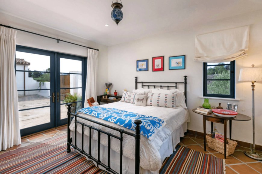 A multicolored striped rug adds a striking accent in this white bedroom with terracotta flooring and a deep blue French door that leads out to the courtyard.