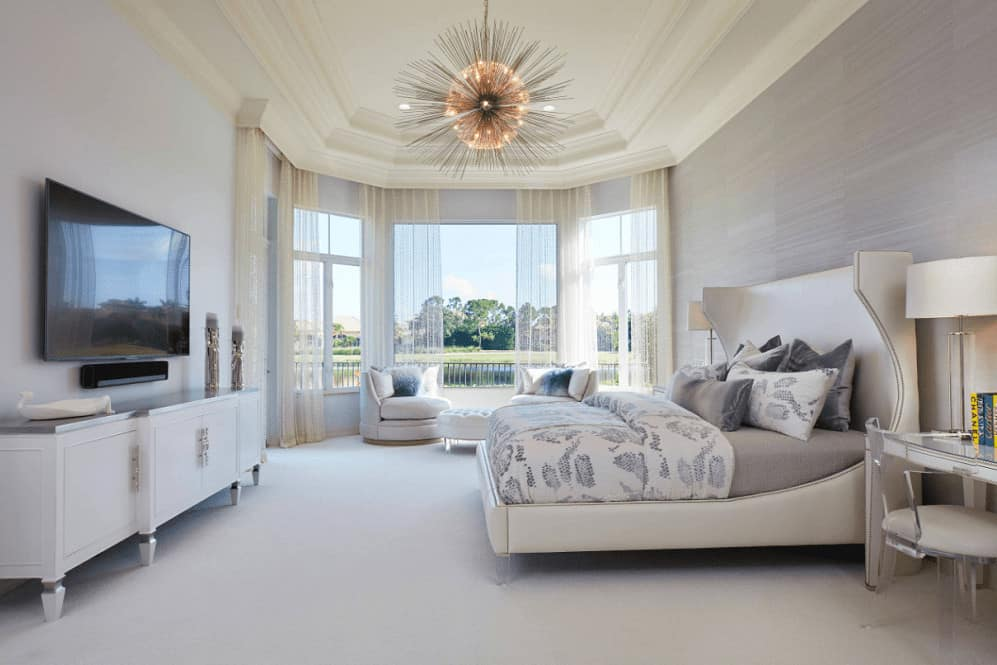 Sleek bedroom illuminated by a gorgeous sunburst chandelier that hung from the tray ceiling. It has round chairs and a wingback bed that faces the television mounted above the white stand.