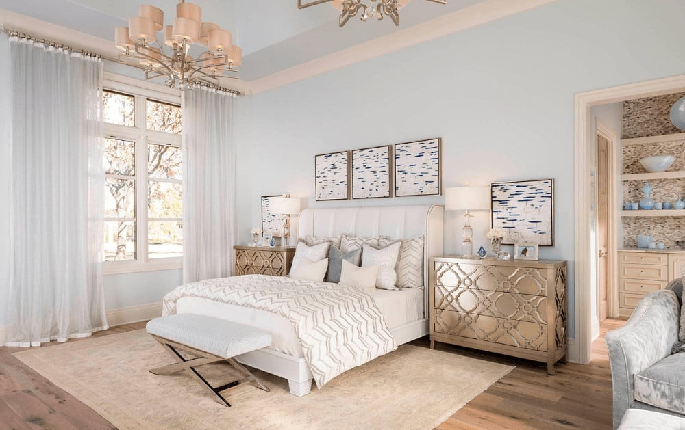 Light and airy bedroom with a white upholstered bed and classy nightstands topped with glass table lamps. It includes a lovely chandelier and sheer curtains covering the white framed windows.