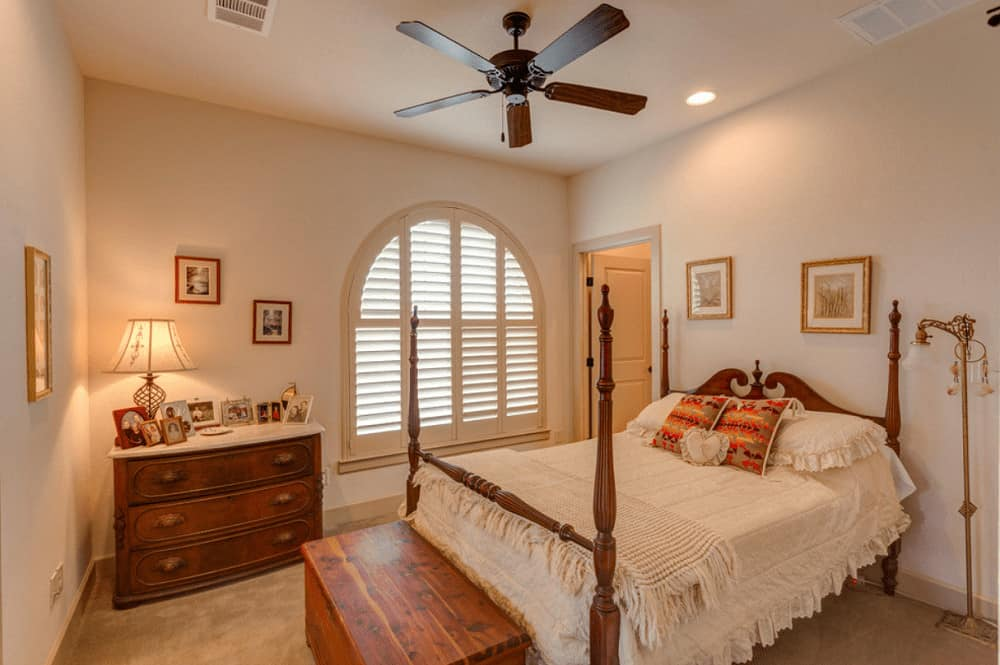 Ambient light from the table lamp and recessed ceiling lights create a warm and cozy feel in this Mediterranean bedroom with a four poster bed and a storage bench that complements the wooden drawer chest.