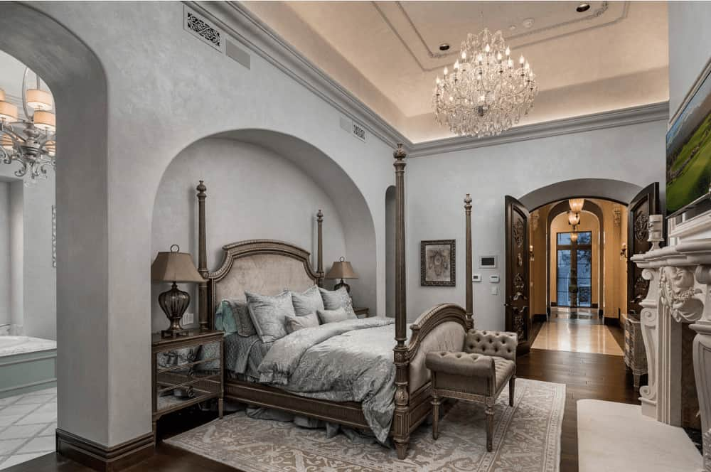 Sophisticated bedroom with a four poster bed and mirrored nightstands with table lamps on top placed on the arched inset wall. It includes a fancy crystal chandelier and a lovely landscape wall art mounted above the carved fireplace.