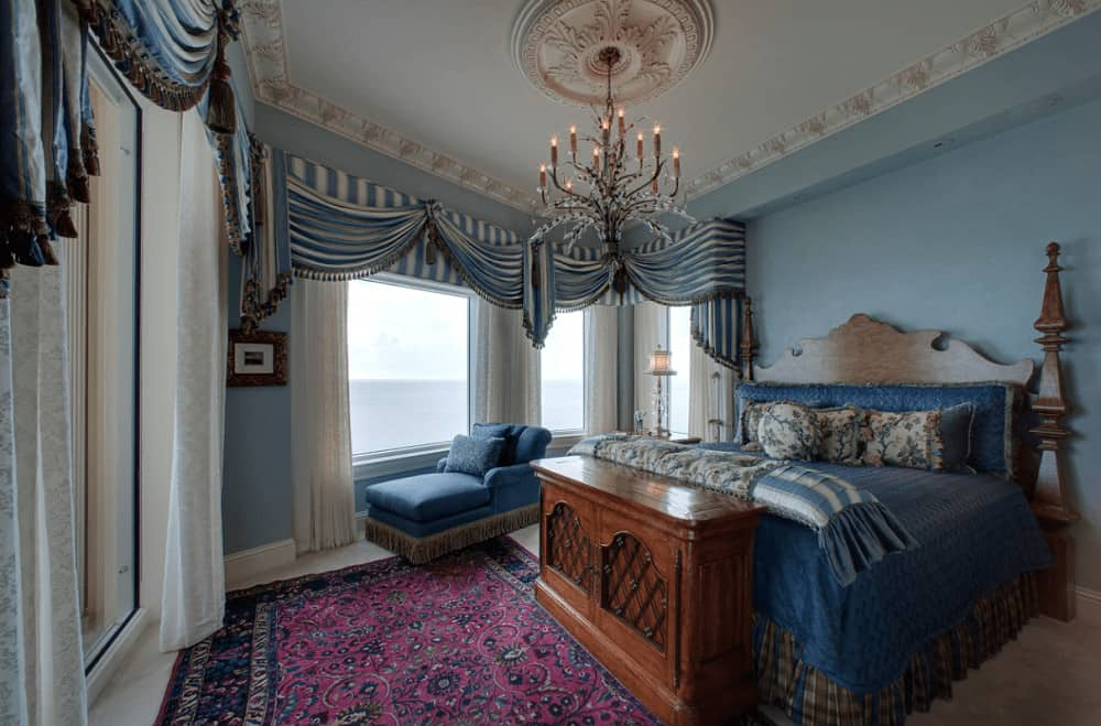 A blue chaise lounge complements the skirted bed in this fabulous bedroom with a glam candle chandelier and classy striped valances covering the picture windows.