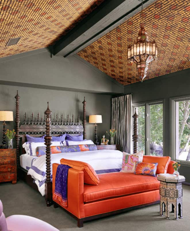 Mediterranean bedroom illuminated by a unique chandelier that hung from the gorgeous cathedral ceiling. It has a four poster bed and orange Cleopatra sofa paired with a stylish table.