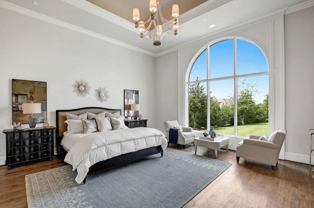 White bedroom decorated with a chandelier and sunburst mirrors mounted above the upholstered bed that's flanked by black nightstands and translucent table lamps. It has natural hardwood flooring and a large arched window framing the lush greenery.