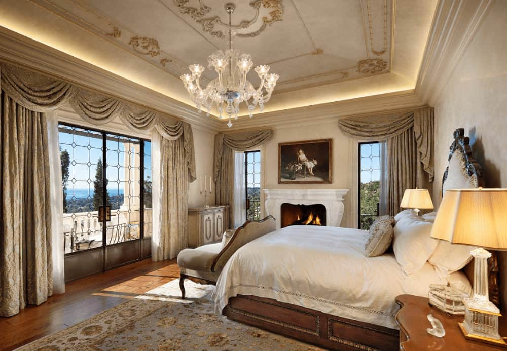 A fancy glass chandelier illuminates this deluxe bedroom offering a white fireplace and wooden bed that's surrounded with glazed windows dressed in classy drapes and valances.