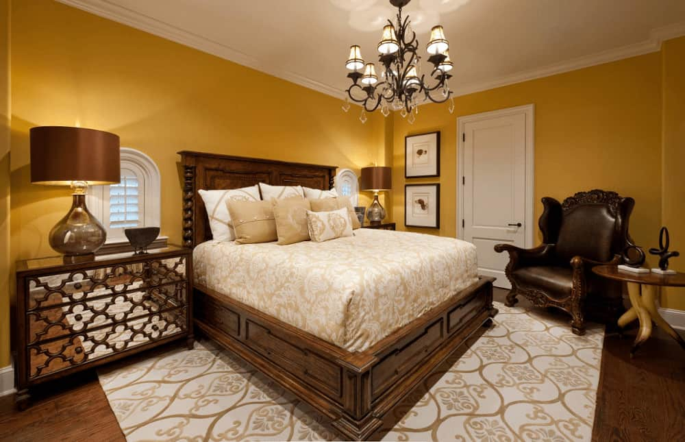 A black leather armchair faces the wooden bed on a patterned area rug over hardwood flooring. It is illuminated by a wrought iron chandelier and glass table lamps that sit on mirrored nightstands.