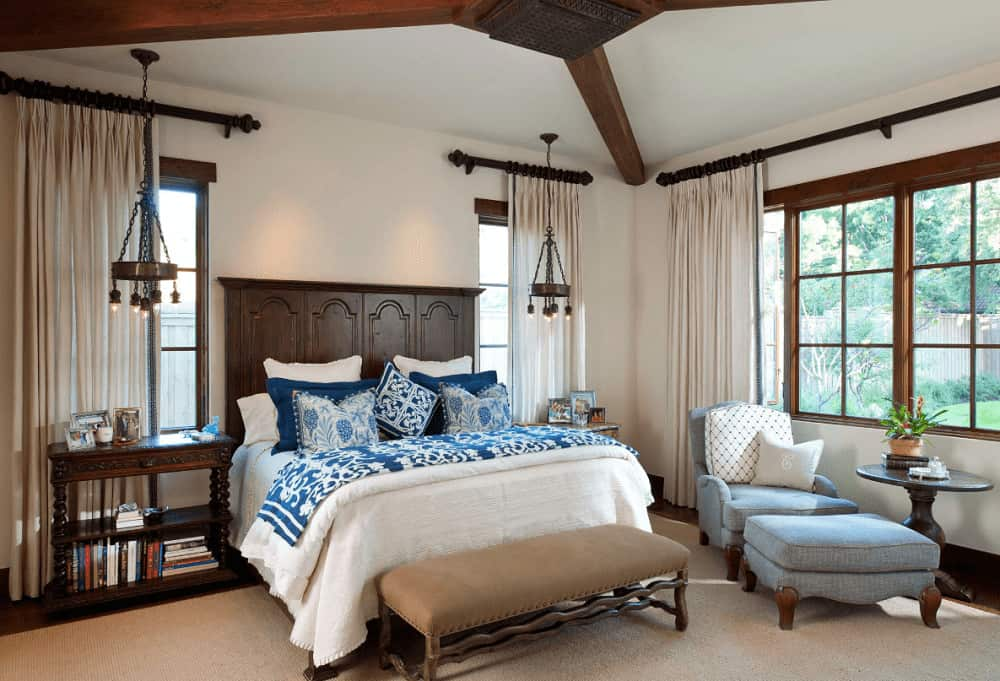A pair of vintage pendant lights illuminate the nightstands in this Mediterranean bedroom with a wooden bed and blue lounge chair that sits next to the round side table.