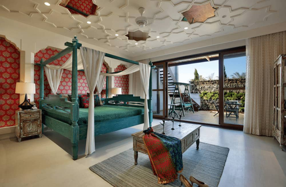 Clad in red patterned wallpaper, this bedroom offers a stylish ceiling and green canopy bed with distressed nightstands on its sides complementing the coffee table that sits on a gray area rug.