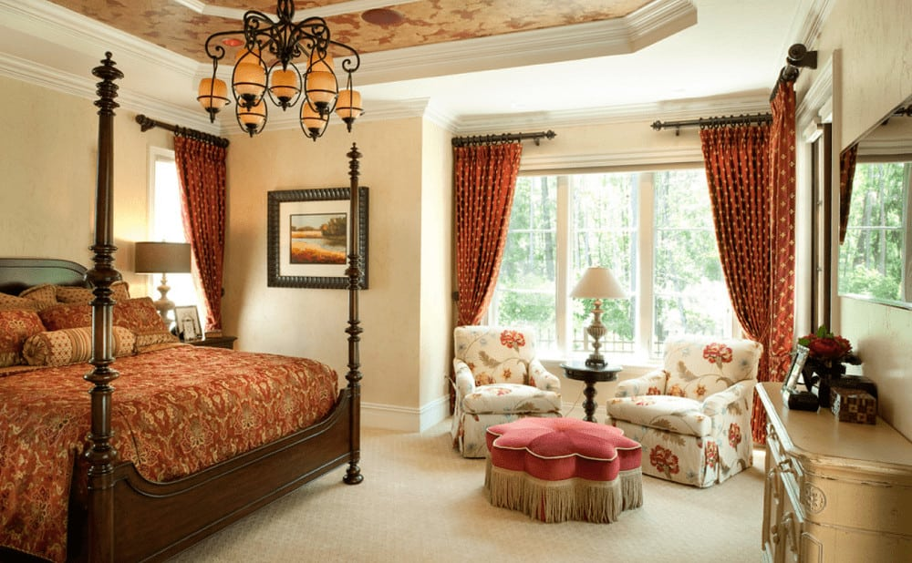 This bedroom showcases a seating area by the full height windows dressed in dotted red drapes along with a wooden four poster bed lighted by an ornate chandelier that hung from the tray ceiling.