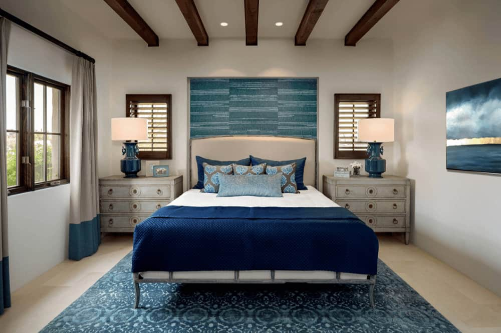 Three drawer nightstands flanked the leather bed in this Mediterranean bedroom with wood beam ceiling and beige tiled flooring topped by a gorgeous blue rug.