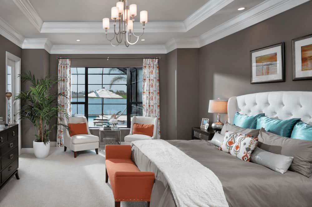 Orange pillows and bench add a warm accent in this gray bedroom featuring upholstered chairs and white tufted bed with black framed wall arts on top.