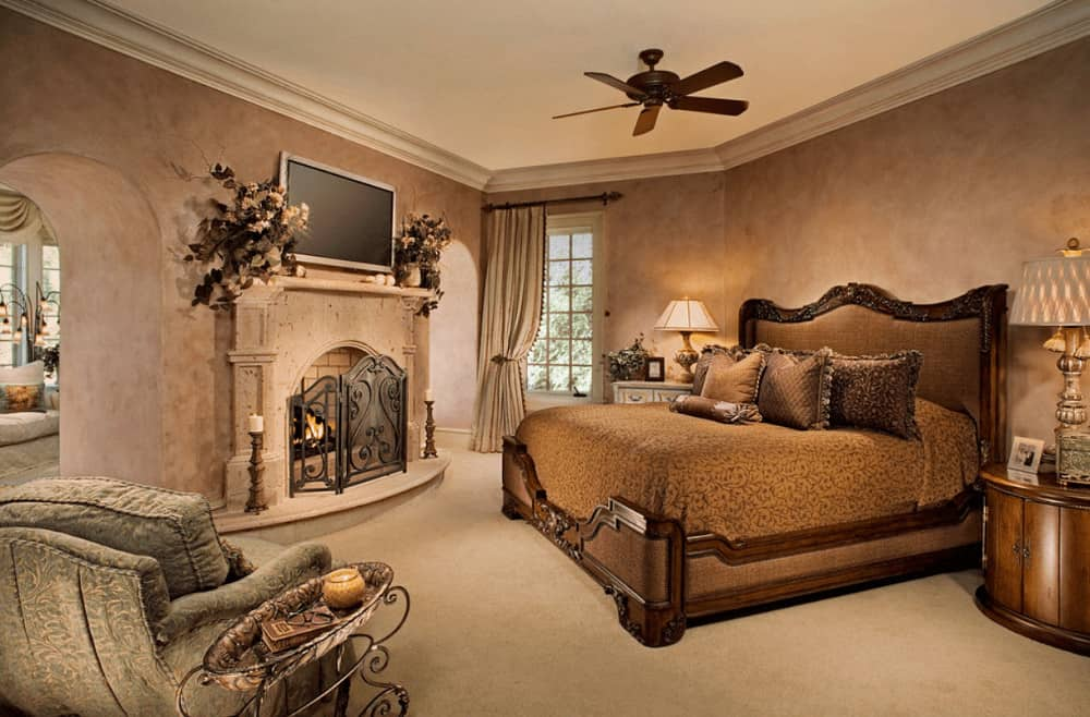 Warm bedroom with a carved wood bed and fireplace enclosed in a three-panel ornate fence. It includes a flat screen TV and an upholstered chair paired with a metal side table.