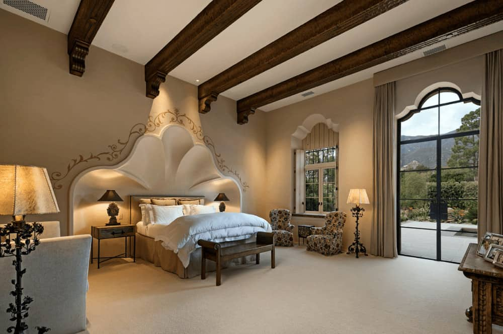 Spacious bedroom with carpet flooring and vaulted ceiling lined with dark wood beams. It has cozy seats and a skirted bed with a wooden bench on its end.