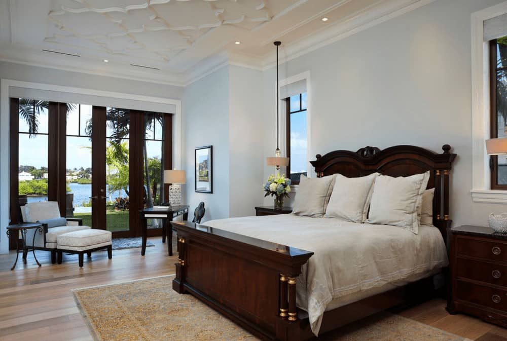 A gray lounge chair faces the dark wood bed that sits on a vintage area rug over wide plank flooring. This room has an ornate white ceiling and glass paneled windows overlooking the magnificent outdoor scenery.
