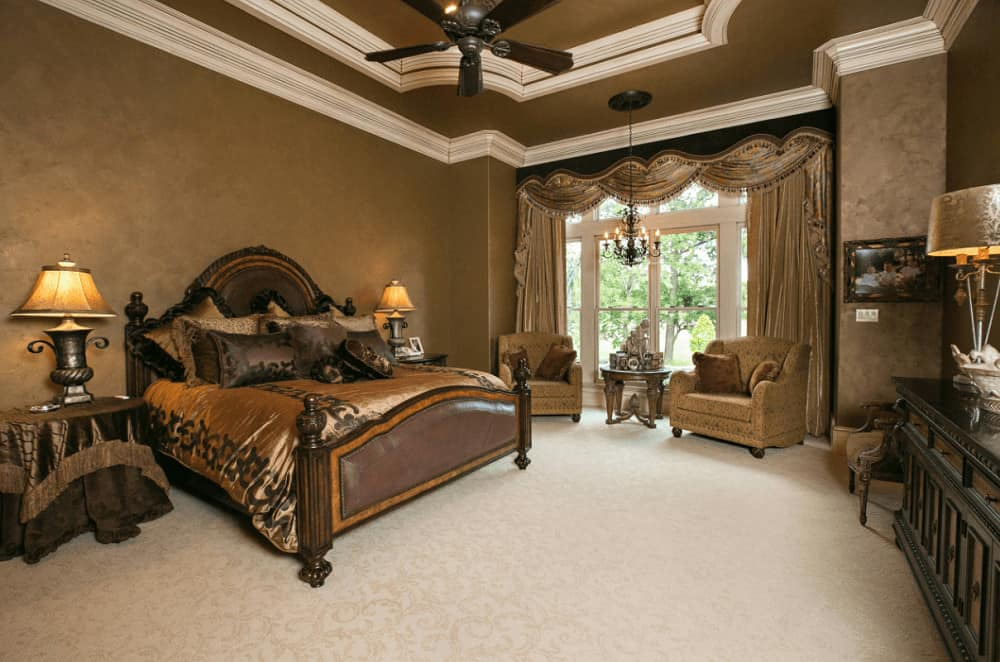 Luxury bedroom showcases a dark wood bed and a seating area by the full height windows dressed in classy silk drapes and valances. It has carpet flooring and a tray ceiling mounted with a bronze fan.