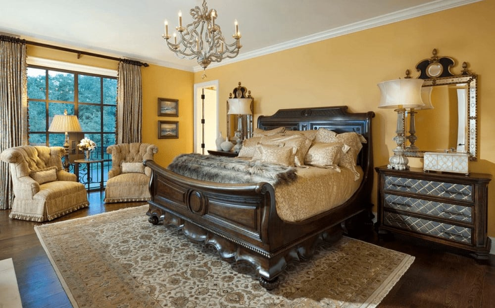 A stylish candle chandelier illuminates this yellow bedroom boasting tufted armchairs and a carved wood bed in between wooden nightstands paired with gorgeous mirrors.