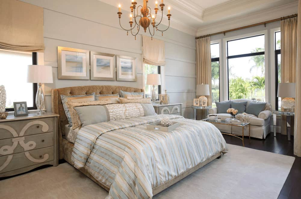 This bedroom offers a skirted sofa and velvet tufted bed dressed in blue striped bedding. It includes distressed nightstands and framed artworks with a cohesive design mounted on the shiplap wall.
